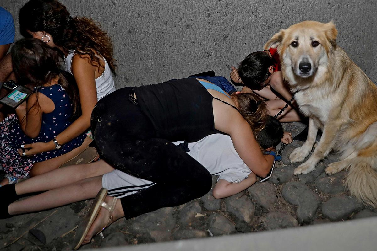 Varios israelíes se refugian bajo un puente en Tel Aviv.