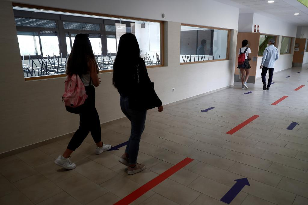 Alumnos de un instituto se dirigen a clase en un pasillo separado por flechas.