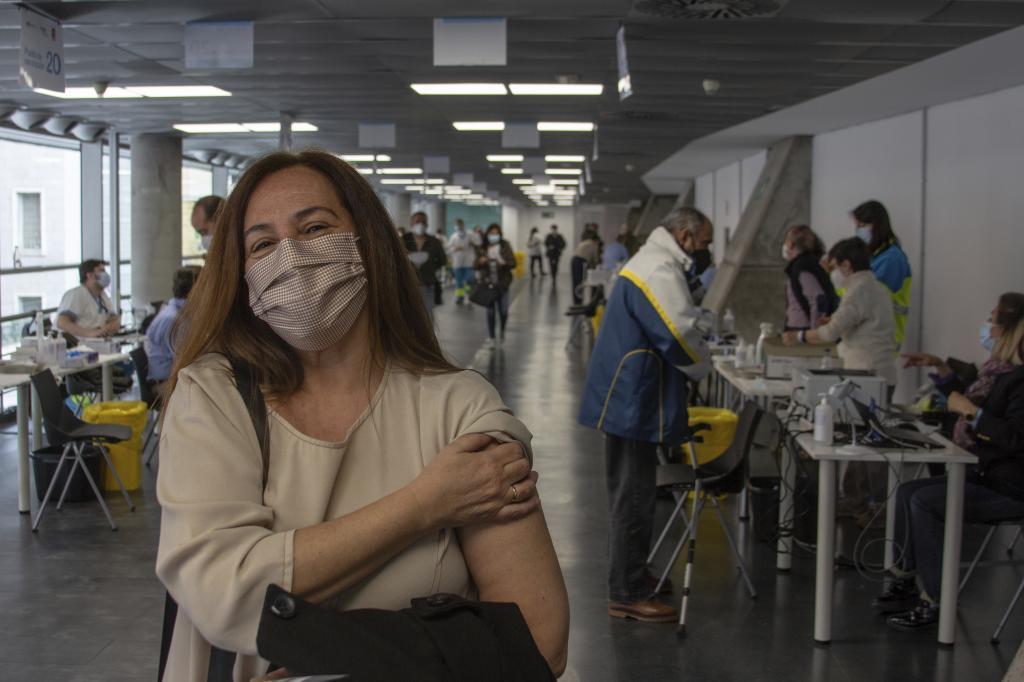 Una mujer posa, tras recibir su vacuna, en el WiZink Center.