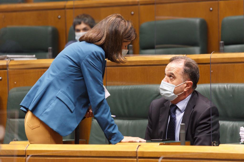 El presidente del PP vasco Carlos Iturgaiz conversa con su compañera Laura Garrido en el Parlamento Vasco.