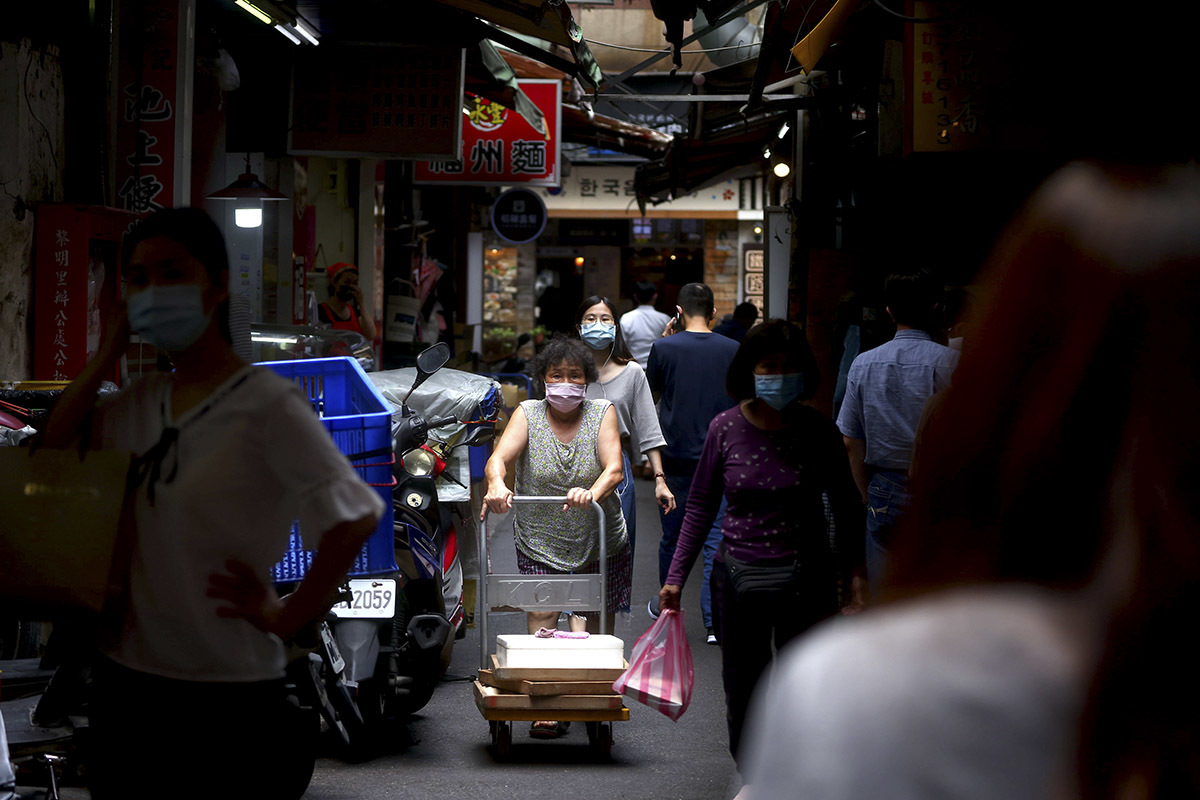 Varias personas con mascarilla pasean por un mercado de Taipei.