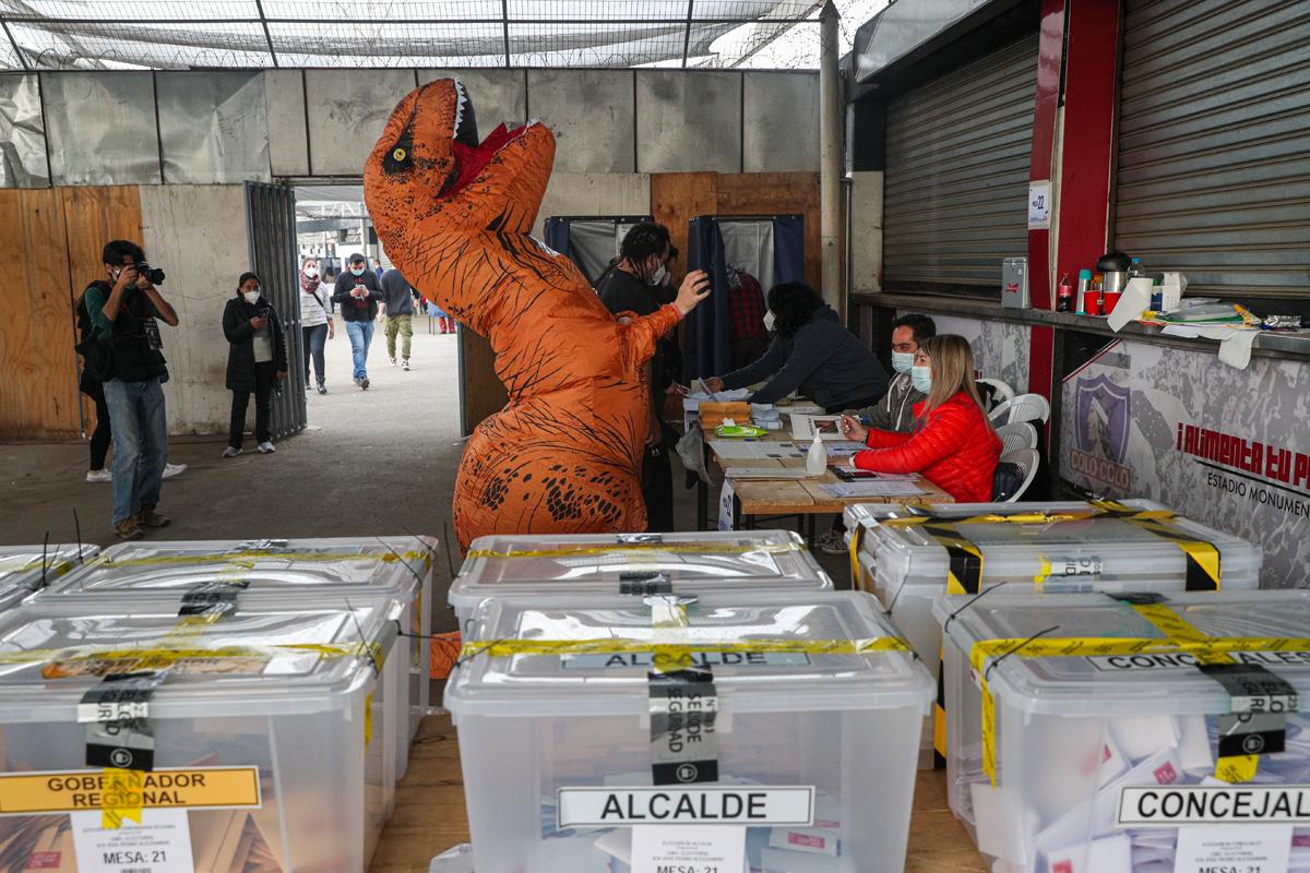 Una persona disfrazada de dinosaurio acude a votar en Santiago de Chile.