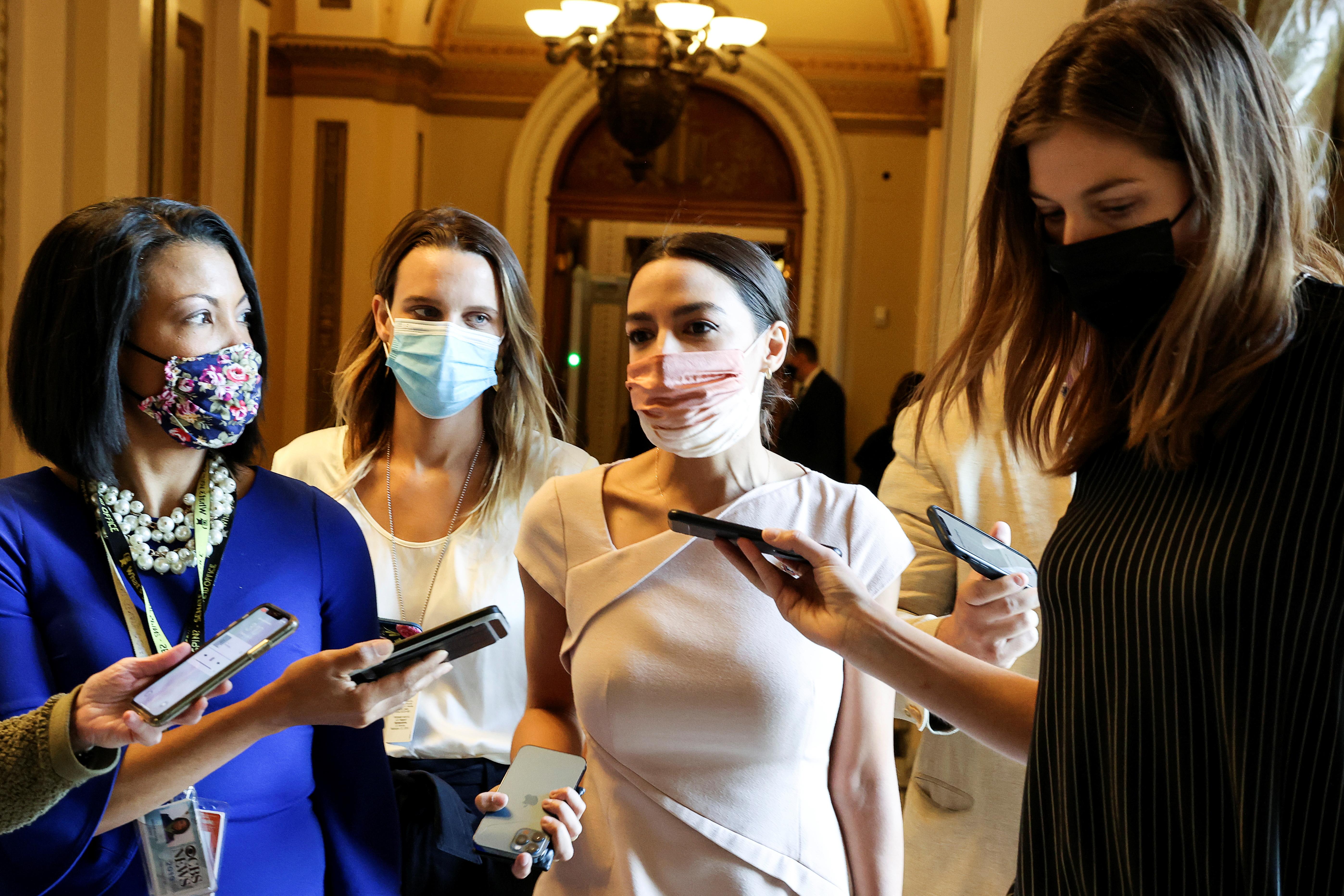 Alexandria Ocasio-Cortez (center) speaks to reporters on Capitol Hill.