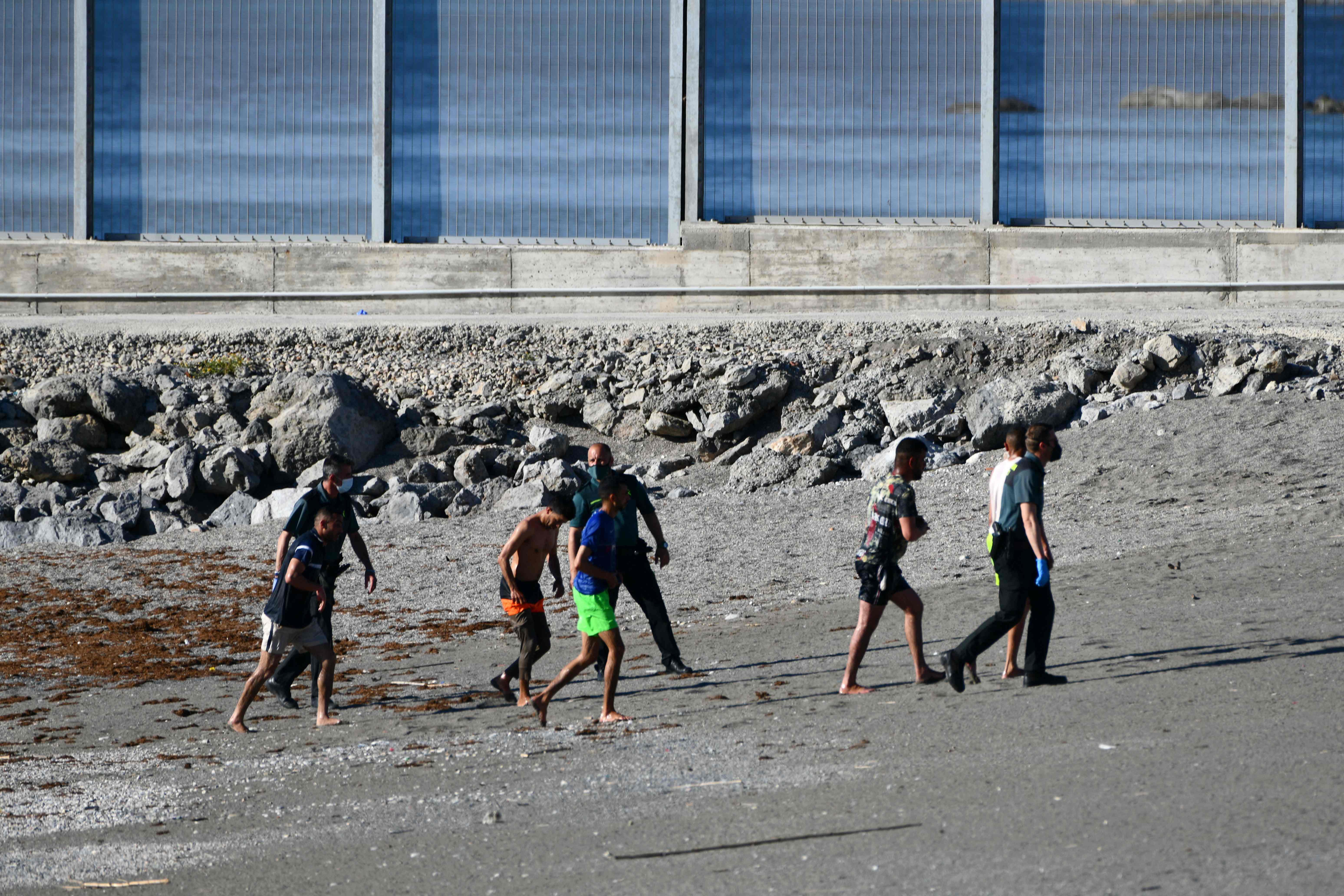 Guardias civiles conducen a varios de los llegados a nado.