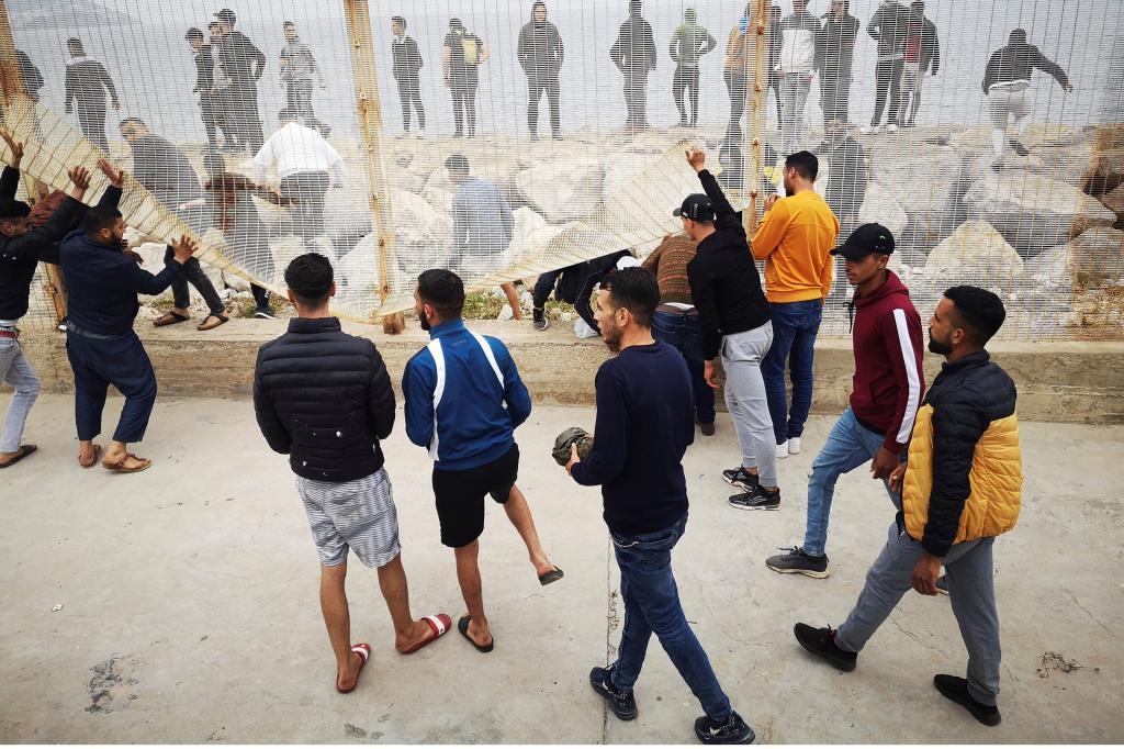 Un grupo de marroquíes trata de derribar una valla para pasar hacia Ceuta.