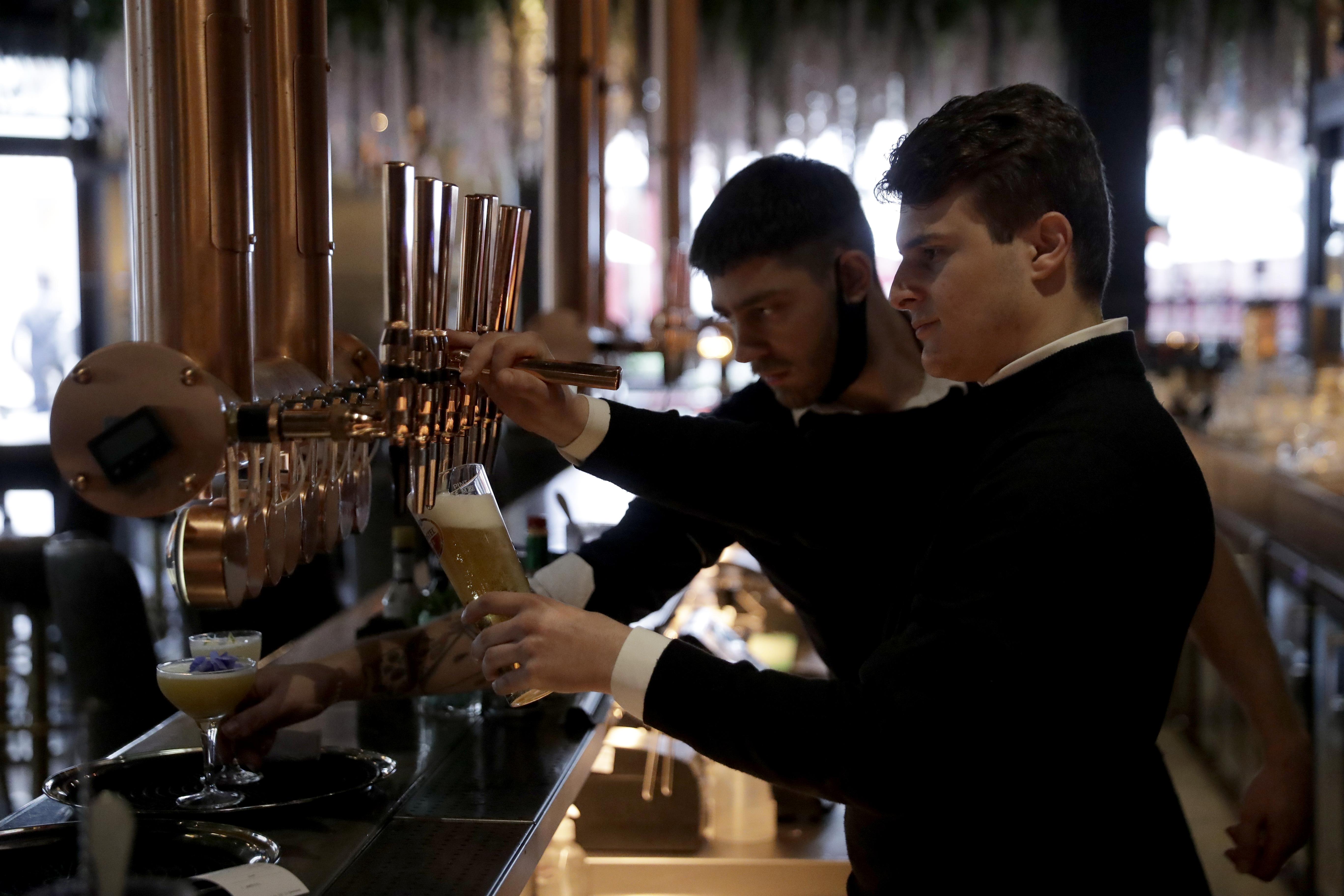Dos camareros preparan bebidas en un bar londinenses.