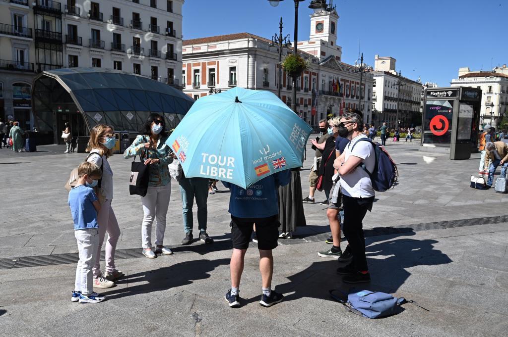 Varios turistas escuchan las explicaciones de un guía turístico en la Puerta del Sol.