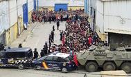 Policías y militares contienen a cientos de inmigrantes irregulares, ayer, en Ceuta.