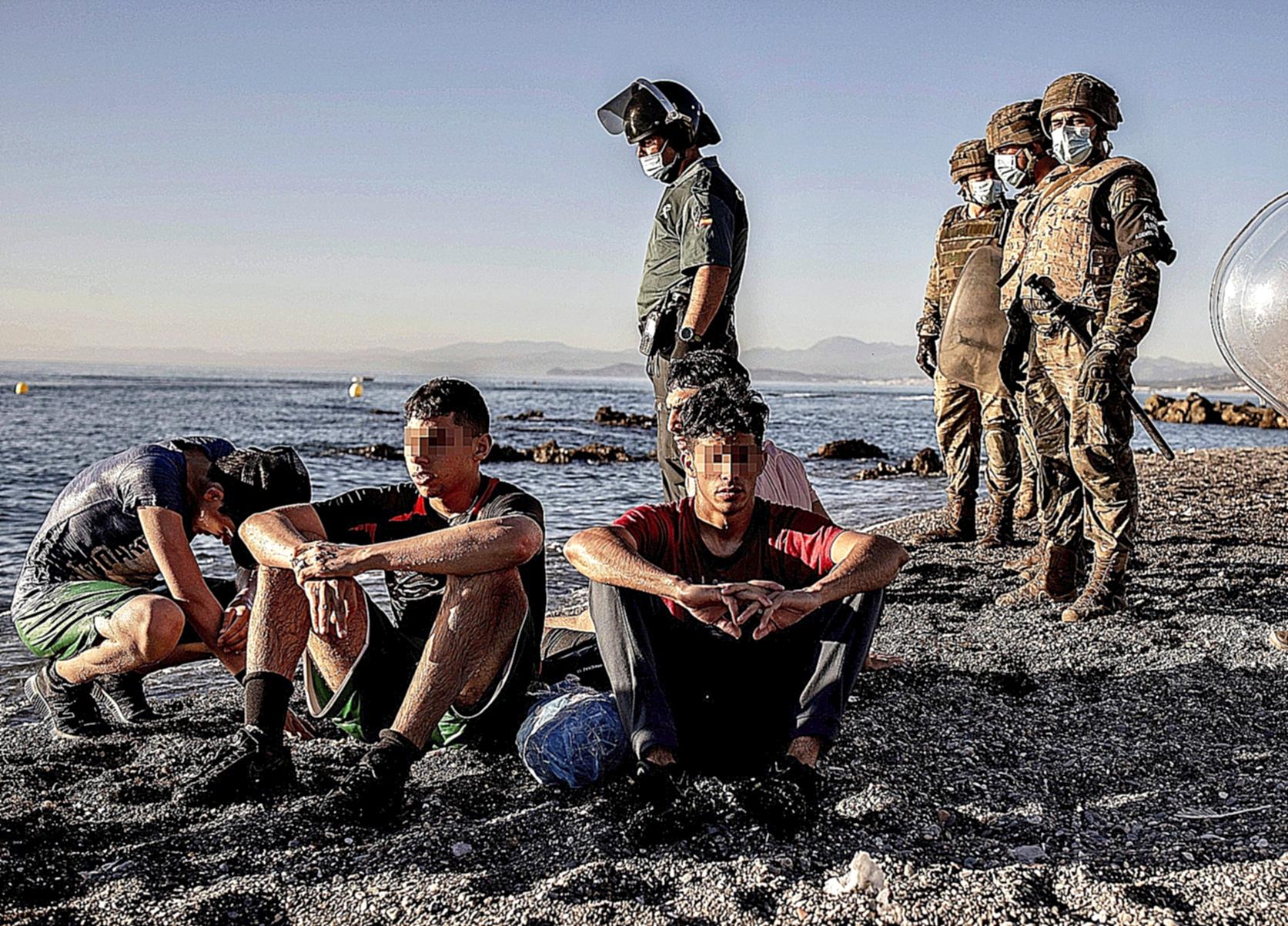 Unos soldados rodean a unos adolescentes marroquíes.