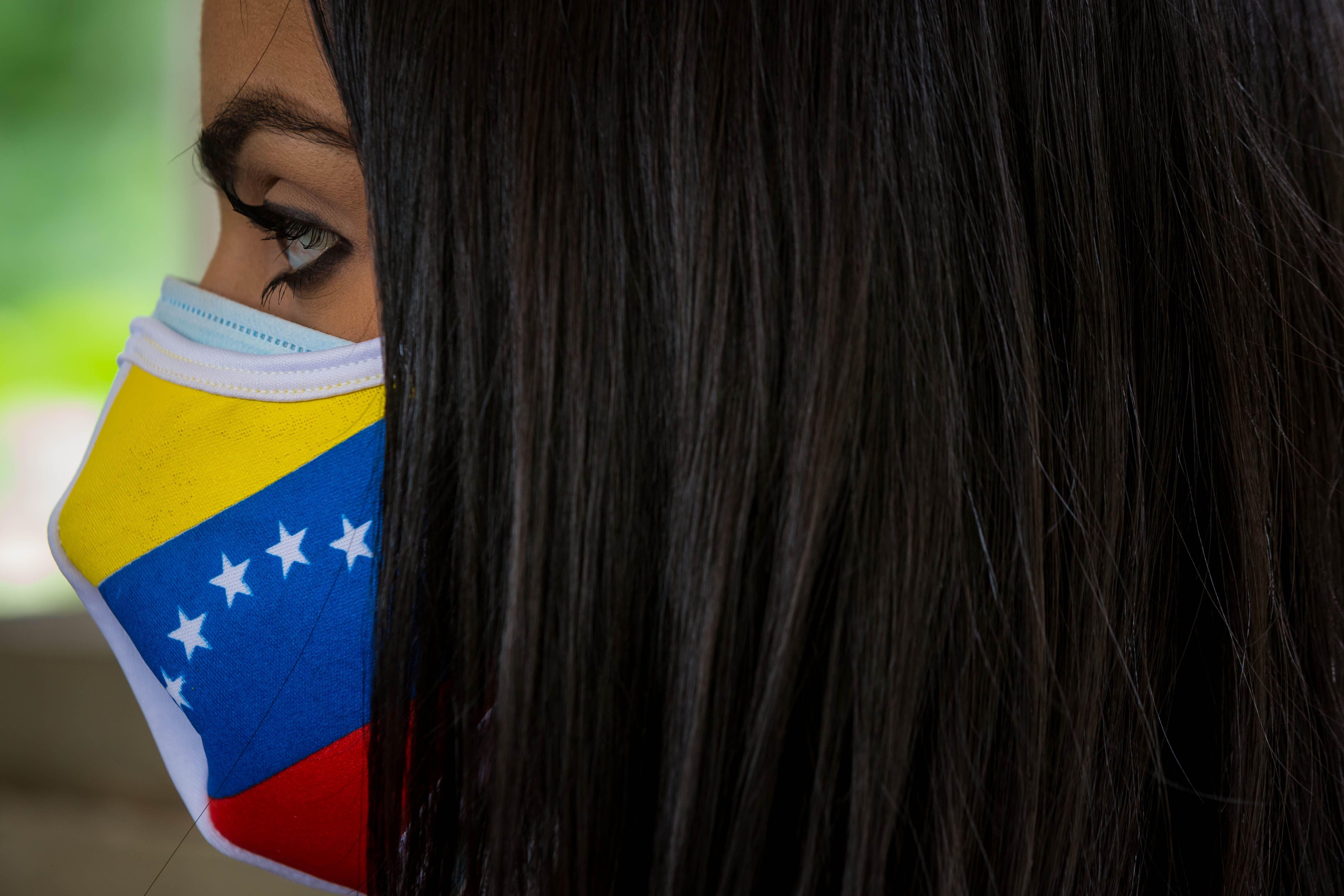 Una mujer con una mascarilla con la bandera de Venezuela en una rueda de prensa de Juan Guaidó.