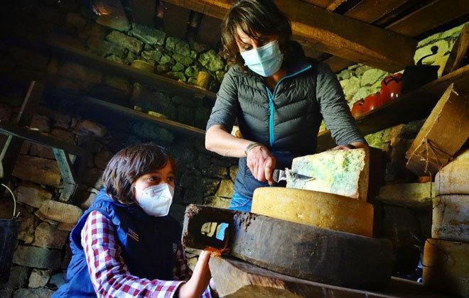 Dos clientes elaborando queso artesanal.