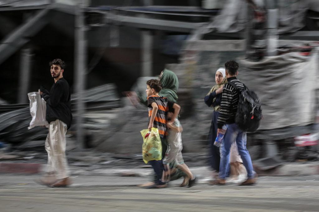یک خانواده فلسطینی هنگام حمله اسرائیل از خانه خود در نوار غزه فرار می کنند