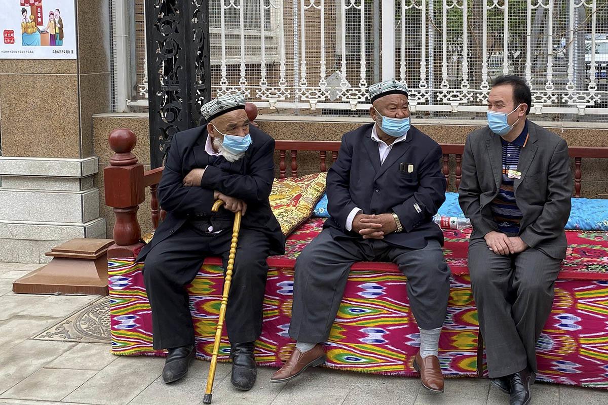 Un hombre conversa con dos ancianos uigures.