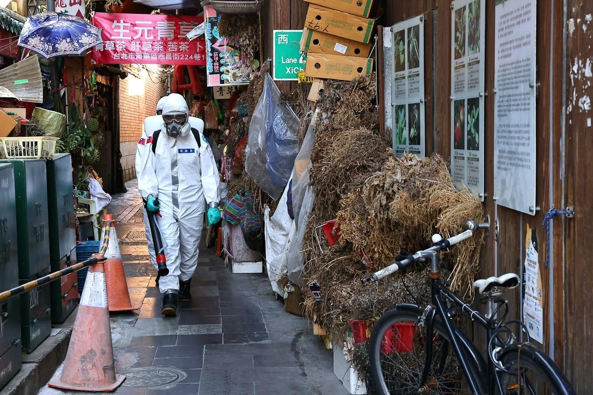 Soldados con trajes de protección desinfectan el barrio rojo de Wanhua.
