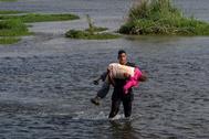 Un hombre cruza Río Grande con una anciana en sus brazos.