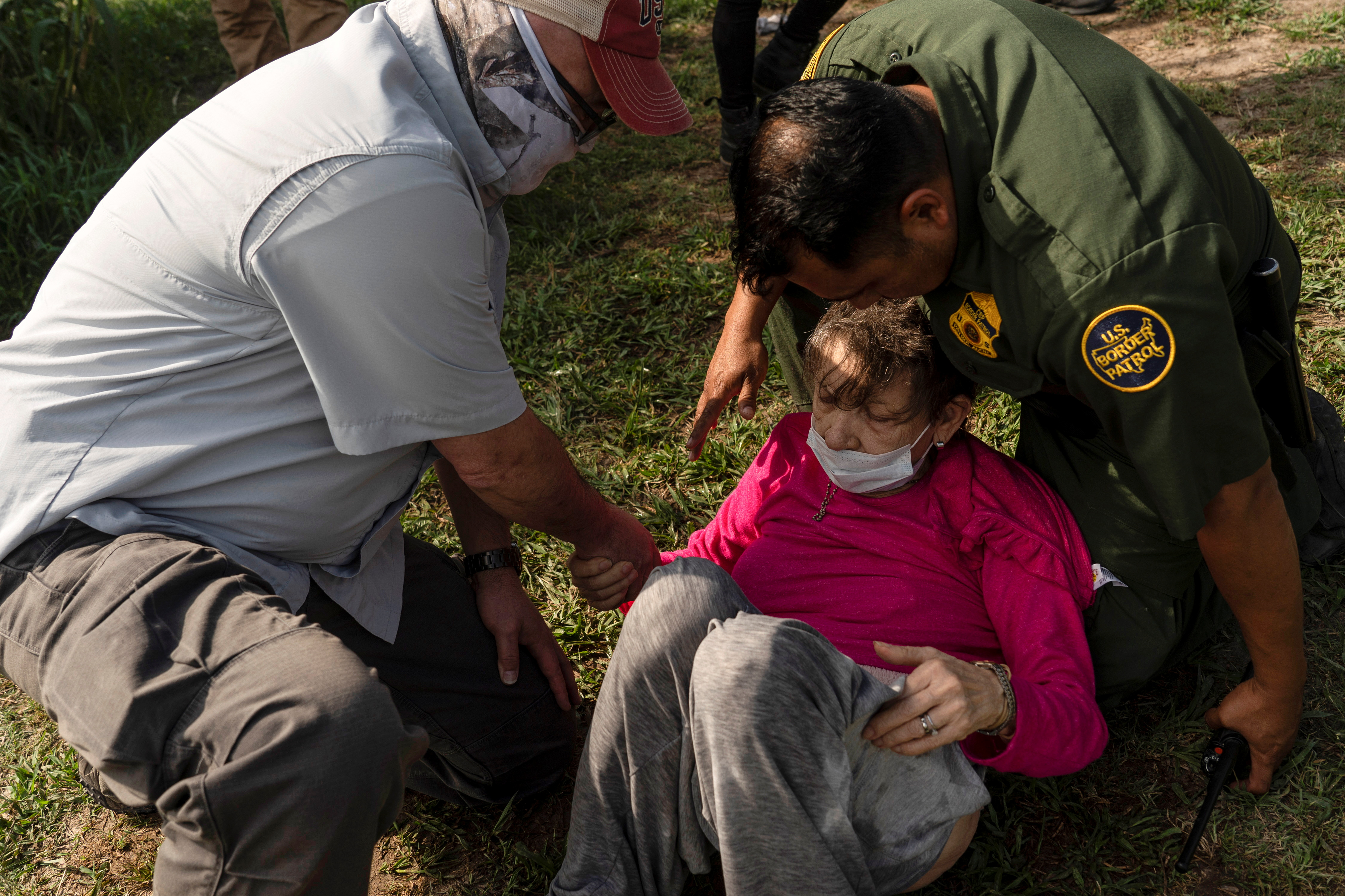 Dos agentes fronterizos ayudan a una anciana venezolana tras cruzar la frontera.