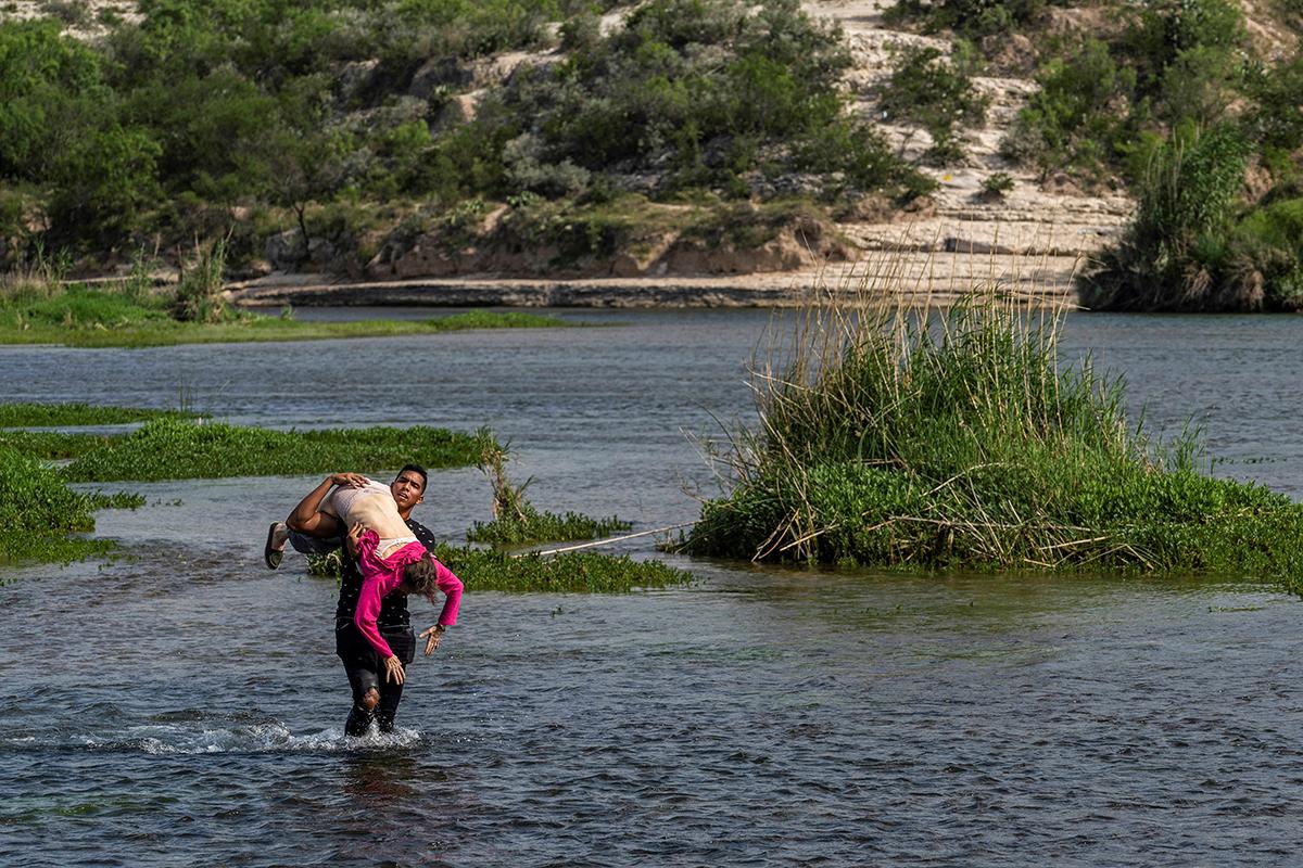 Un migrante venezolano carga a una anciana mientras cruza el río Grande, EEUU.