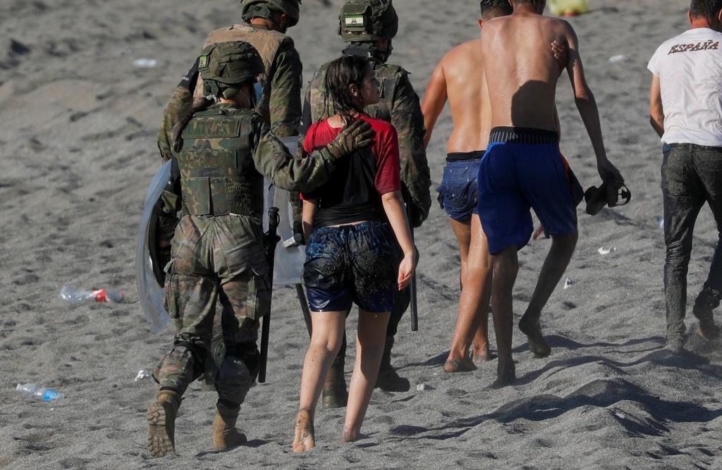 Marroquíes llegados a nado a Ceuta, custodiados por militares españoles en la playa.