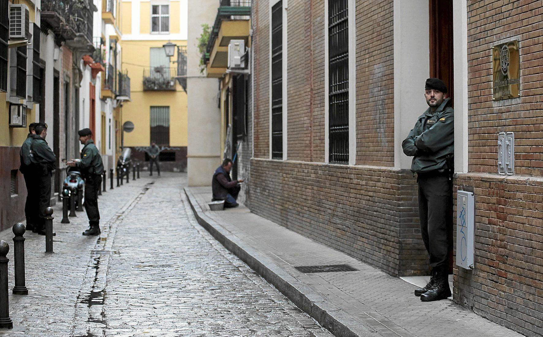 Agentes de la UCO de la Guardia Civil escoltan la entrada de la antigua sede regional de UGT en Sevilla, en el registro de diciembre de 2013.