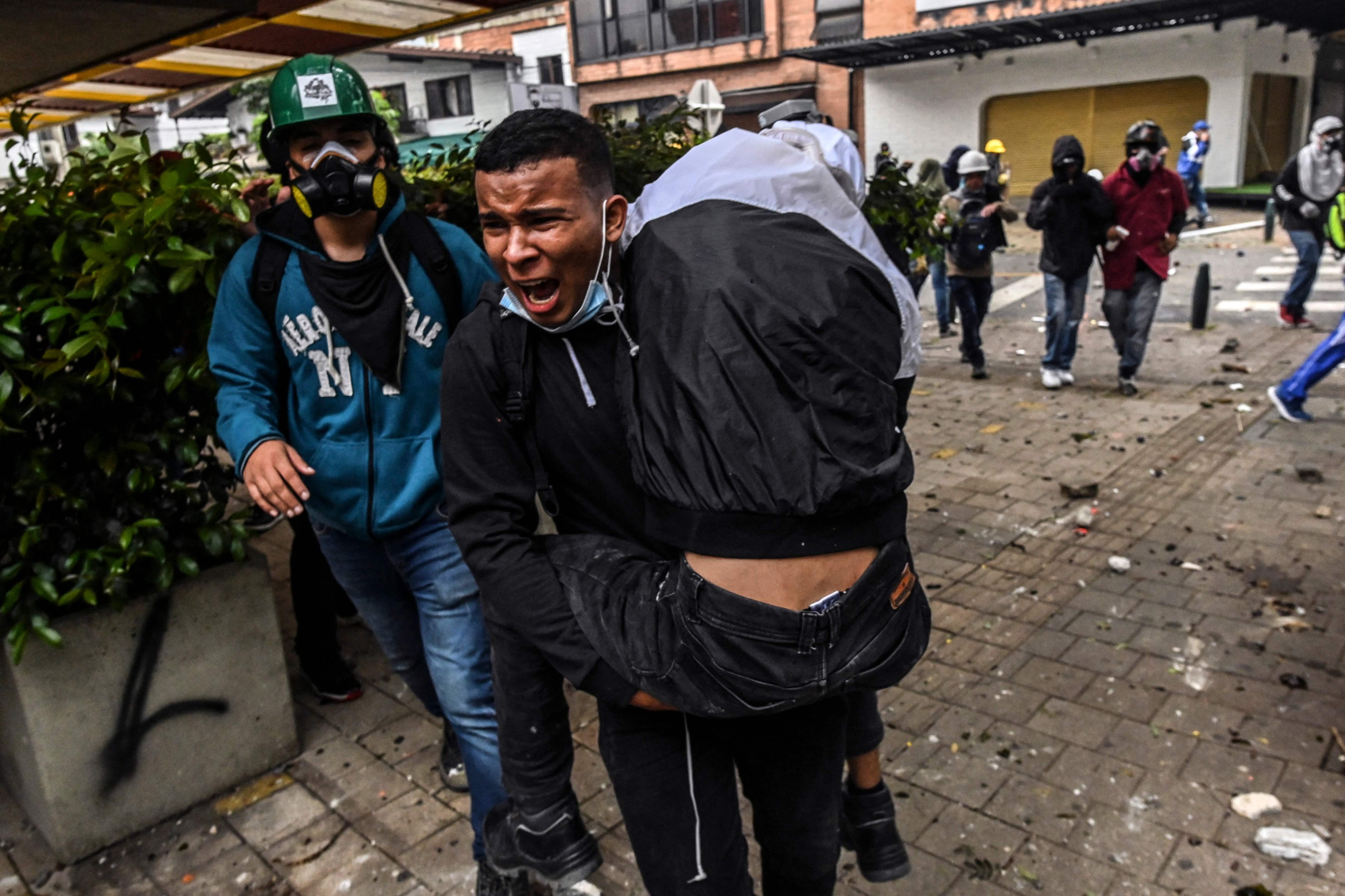 Un hombre carga con un herido en una protesta en Medellín.