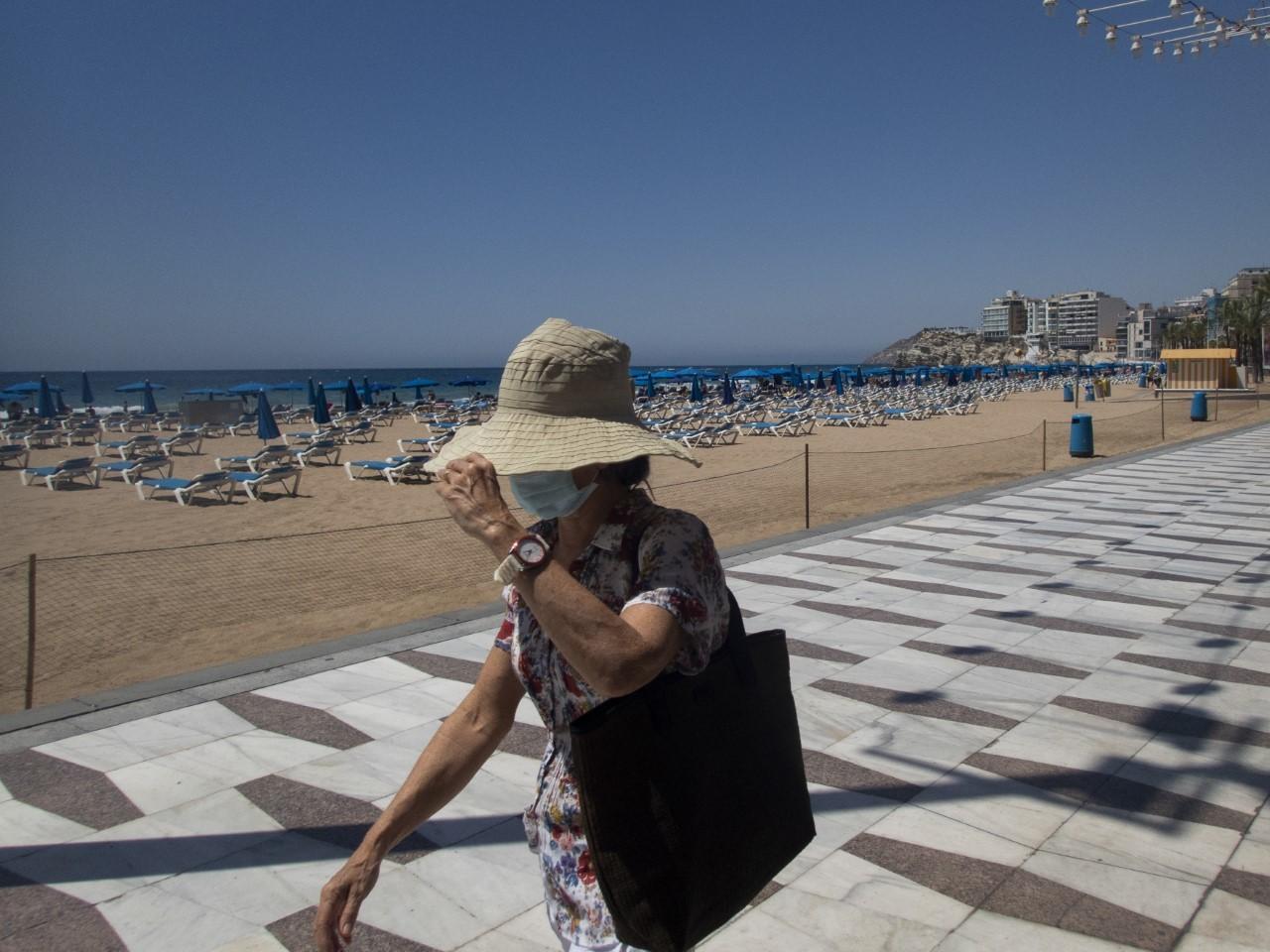 Una mujer se protege del sol en Benidorm el pasado julio