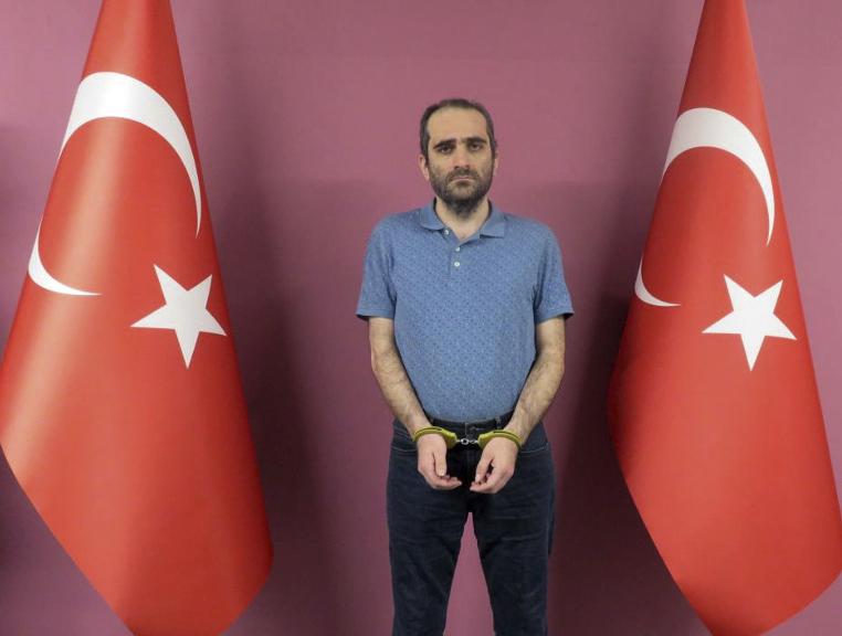 Selahaddin Gülen, esposado entre banderas turcas.