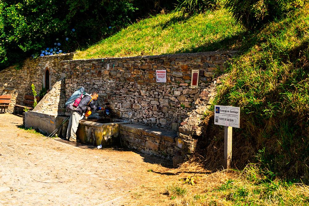 Peregrino cogiendo agua en la Fuente de San Juan.