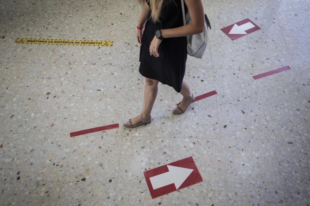 Una maestra camina por el pasillo de un colegio.