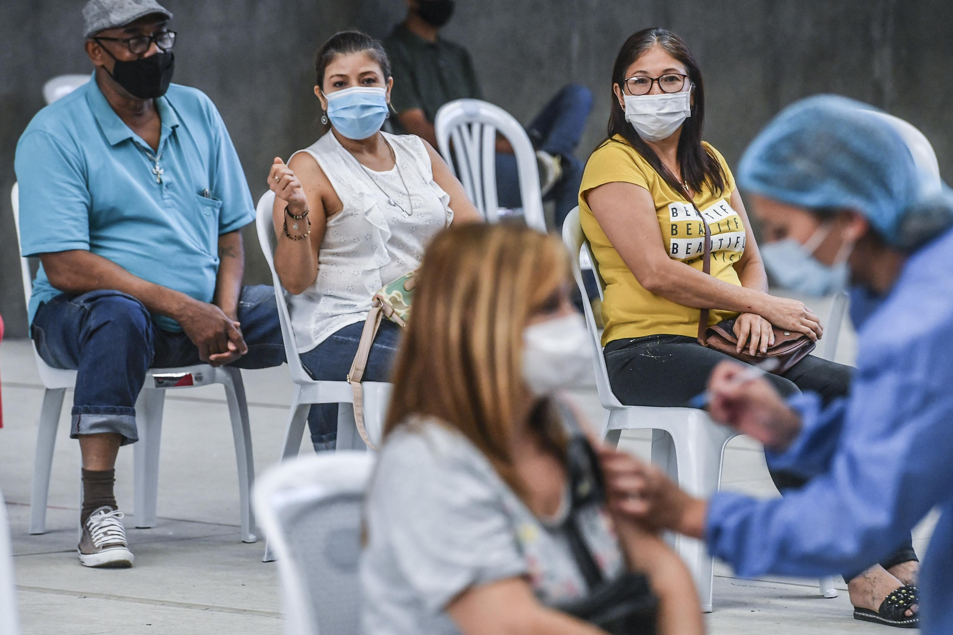 Varias personas esperan a ser vacunadas, en Medellín.