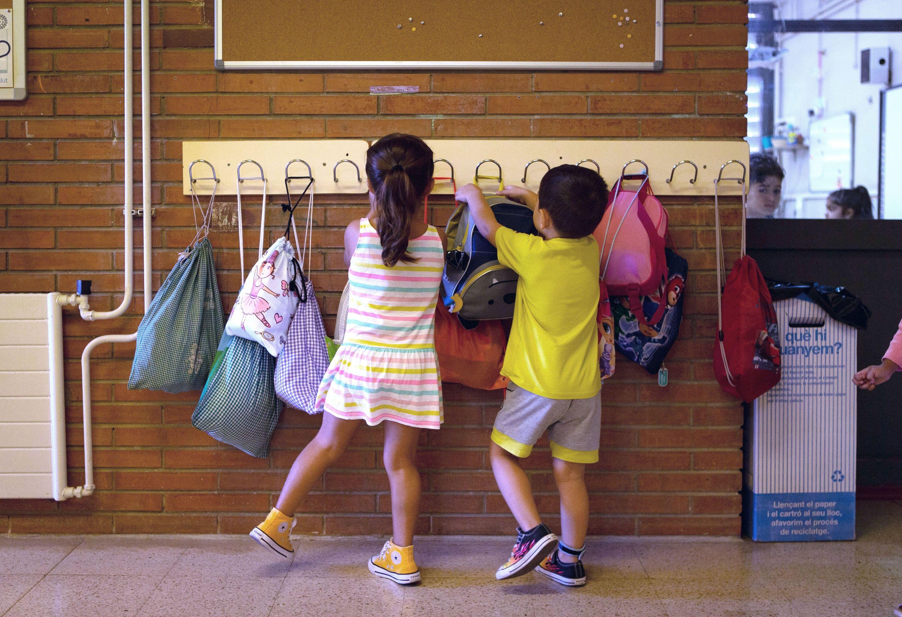 Dos niños cuelgan sus mochilas en la Escola Catalonia de Barcelona.