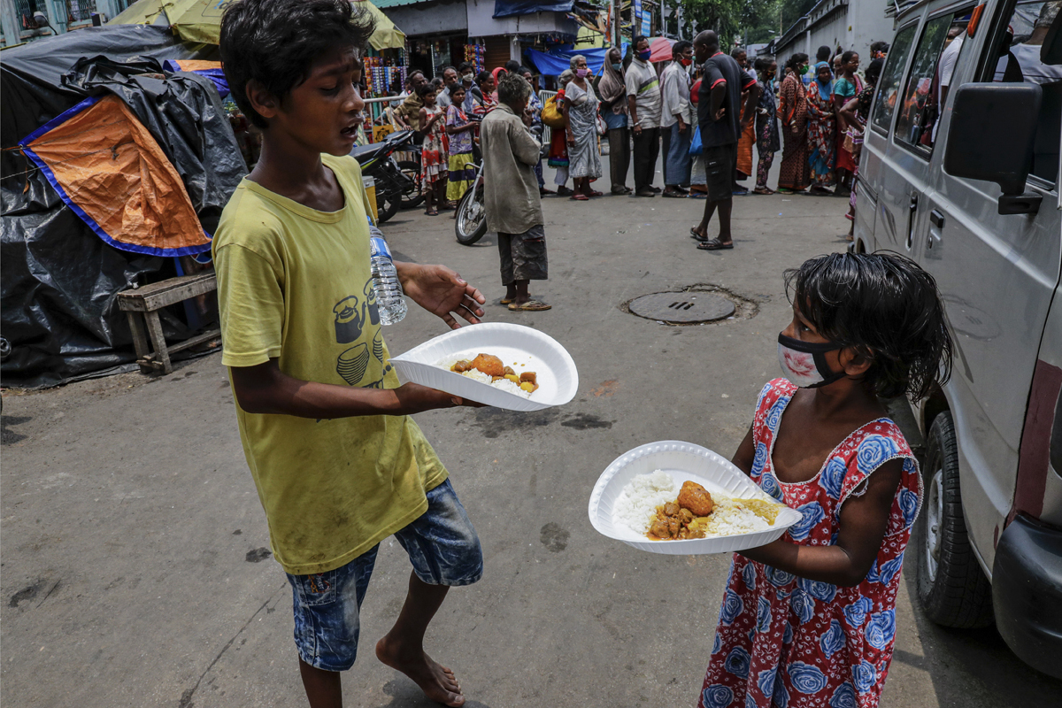 Dos niños reciben comida gratuita en Calcuta, India.