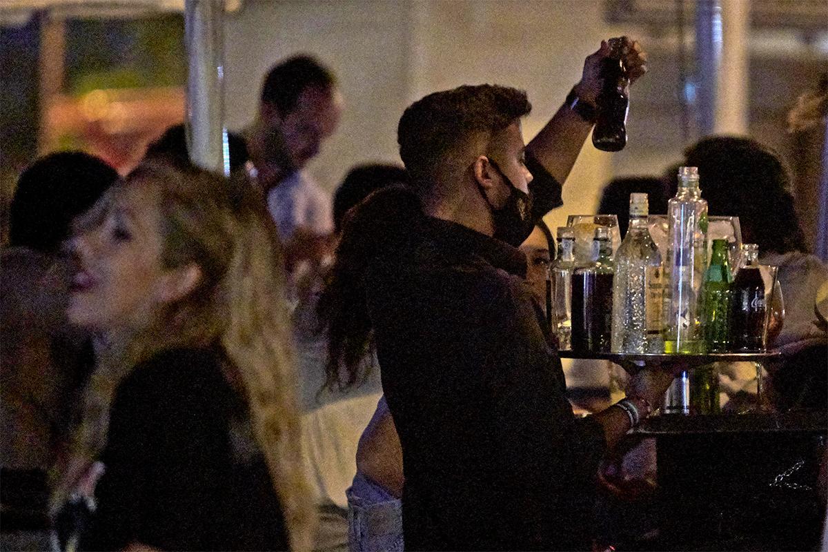 Un camarero sirve copas en un bar de Sevilla.