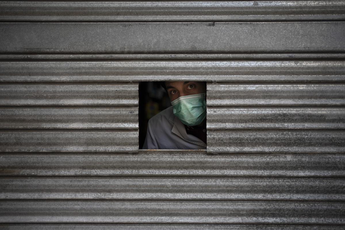 Un farmacéutico se asoma al exterior durante el confinamiento en Igualada en 2020.