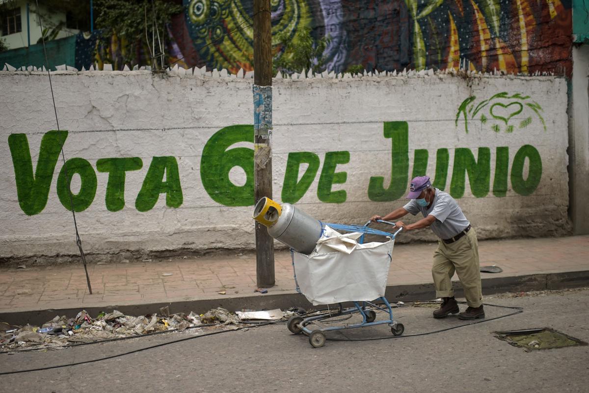 مردی در مقابل نقاشی دیواری انتخاباتی در Ciudad de M قدم می زند