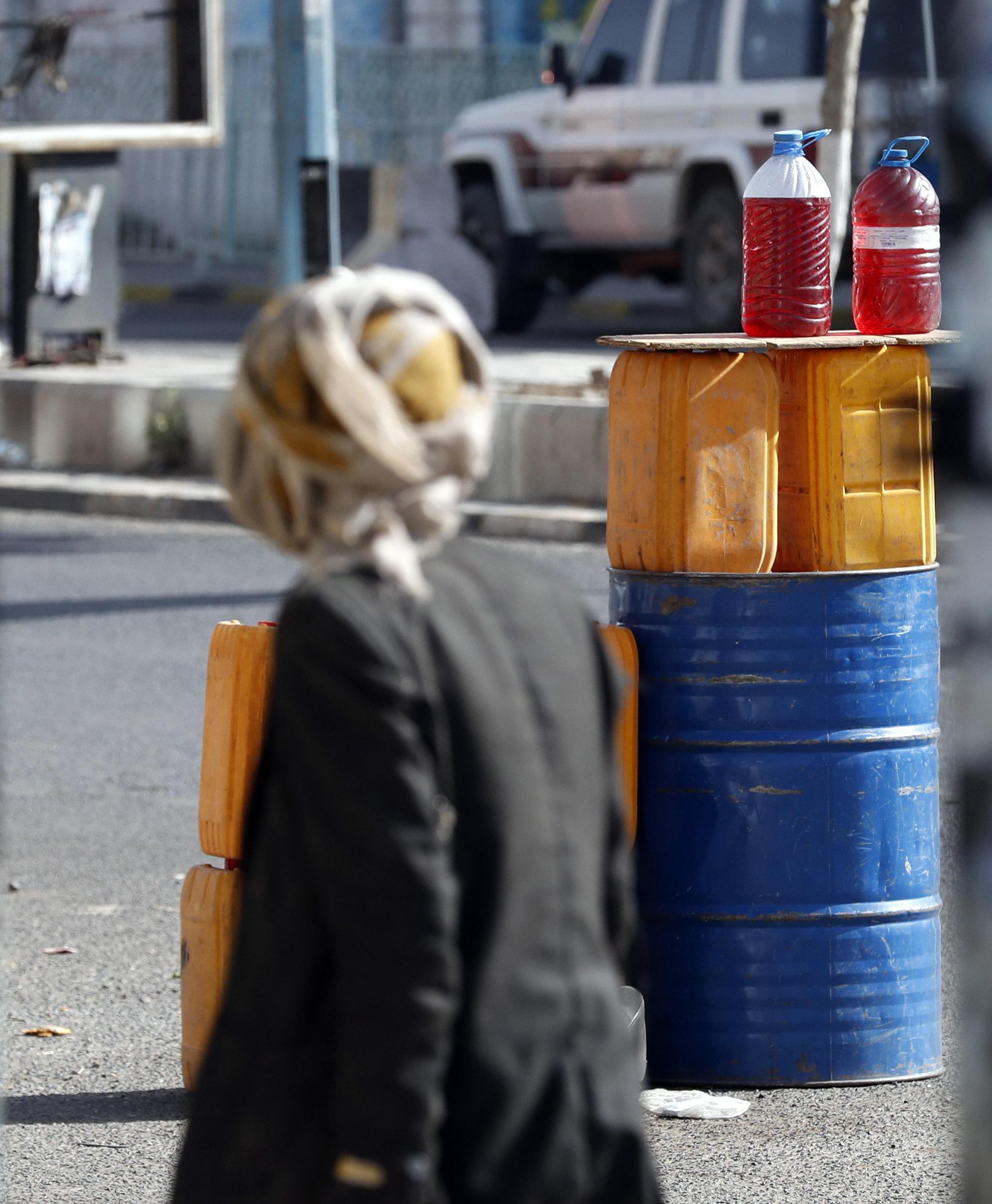Un yemení camina junto a unos barriles de petróleo de venta en la calle.