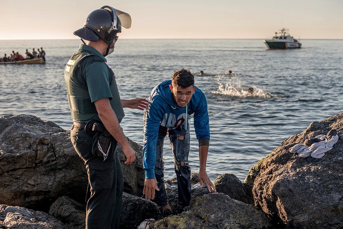 Un soldado del ejército ayuda a un inmigrante a su llegada a la playa de El Tarajal.
