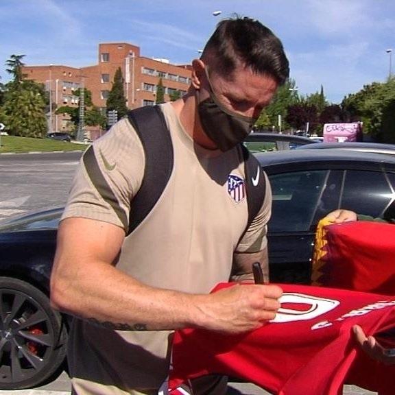 Fernando Torres firma una camiseta.