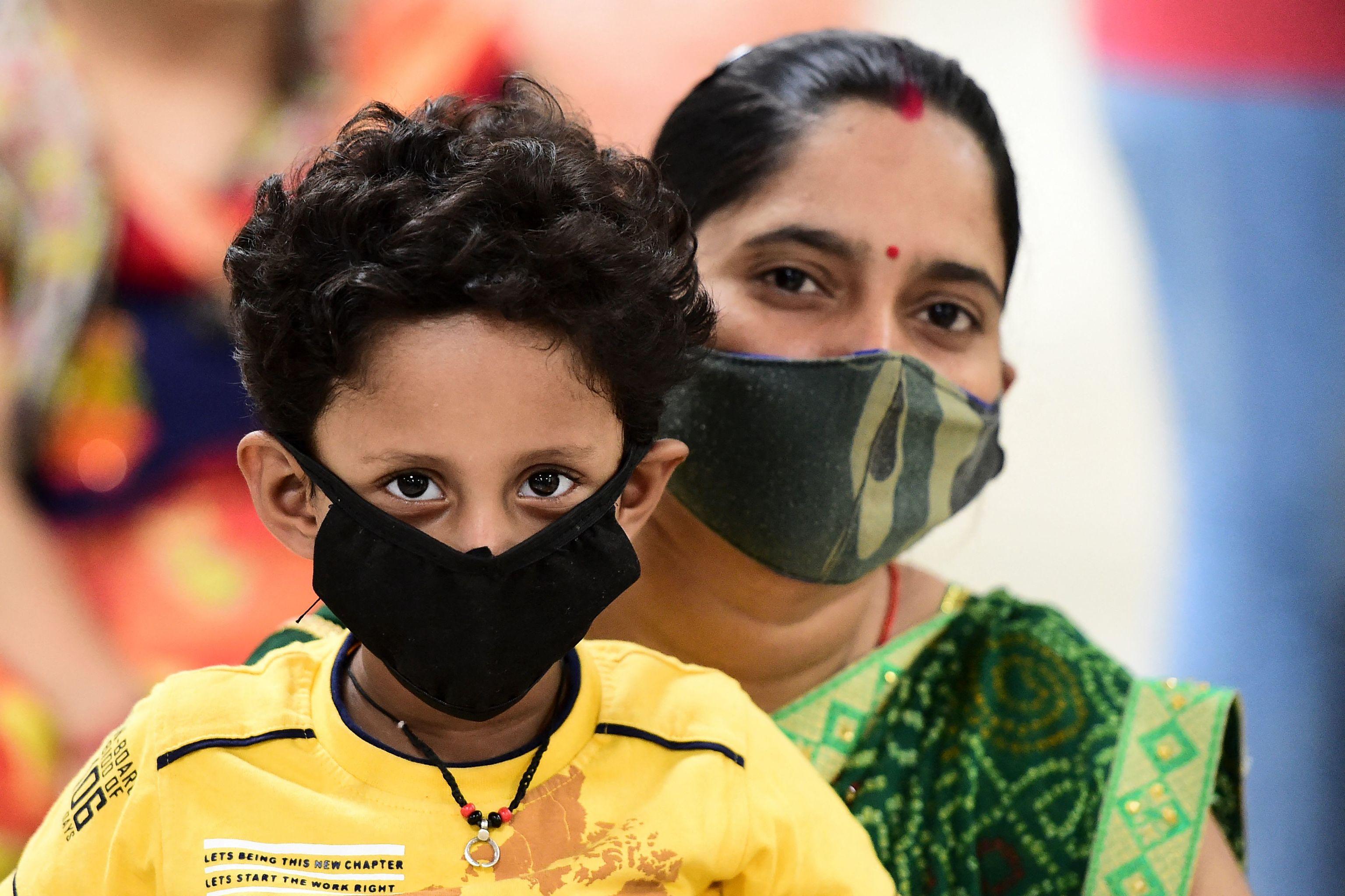Una mujer con su hijo espera para recibir la vacuna del Covid, en Allahabad (India).