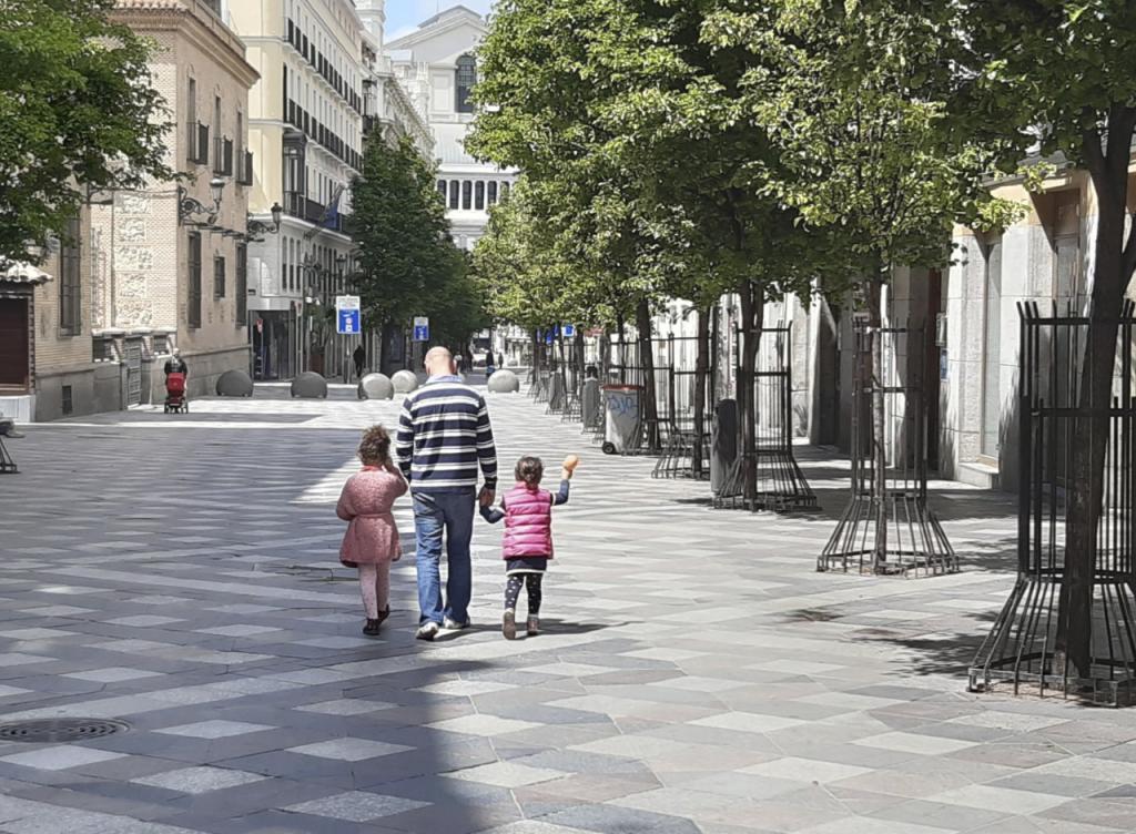Un padre pasea con sus hijas por el centro de Madrid.
