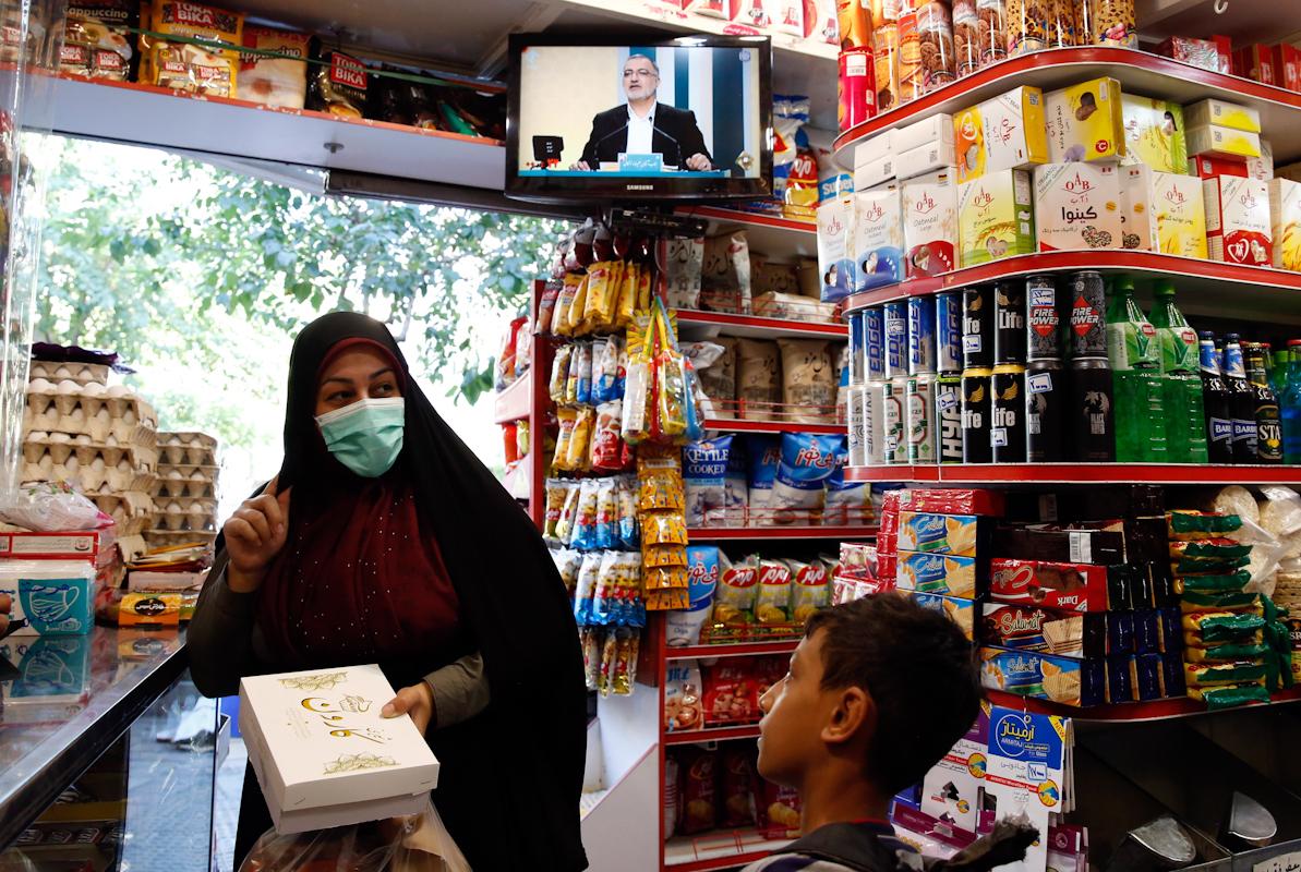 Una iraní compra mientras se televisa el debate de candidatos en una tienda de Teherán.