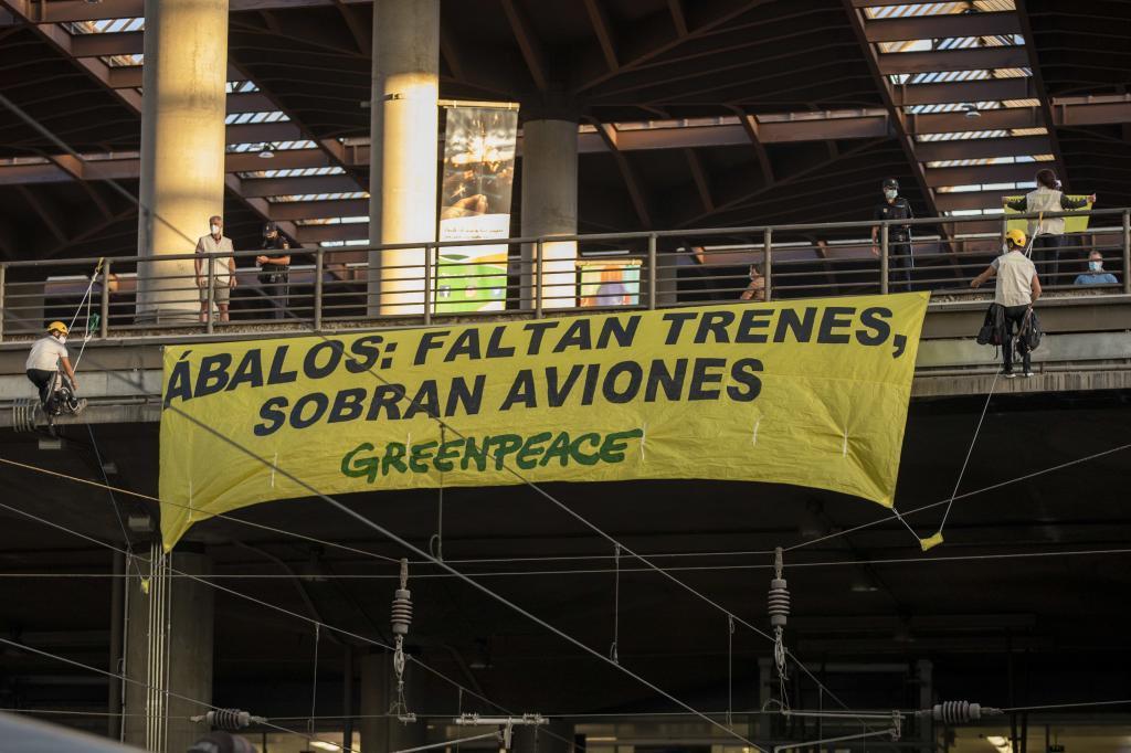 Activistas de Greenpeace despliegan una pancarta sobre las vías del tren para denunciar la falta de trenes en un verano marcado por la Covid-19