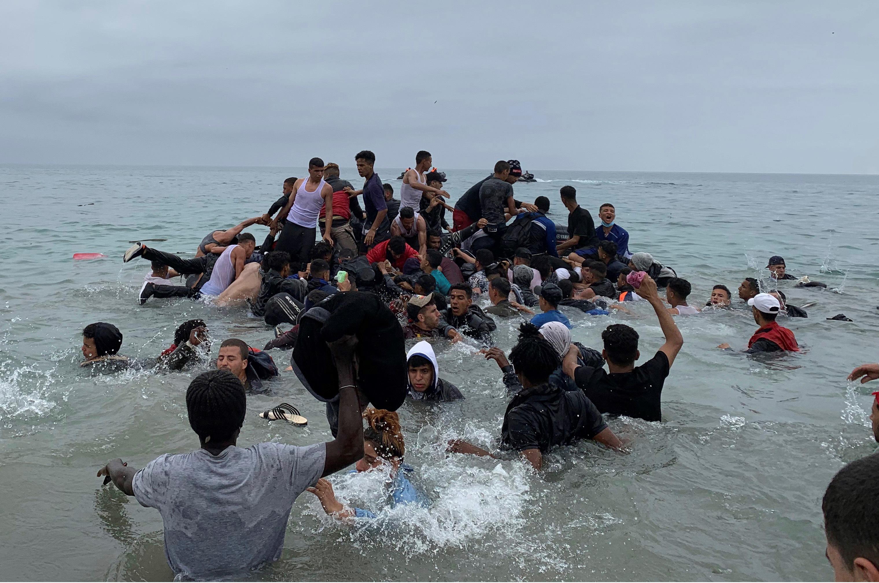 Un grupo de personas se hacen con una embarcación de las autoridades marroquíes en la playa de la localidad de Fnideq (Castillejos) para cruzar los espigones de  lt;HIT gt;Ceuta lt;/HIT gt; este martes en una avalancha de inmigrantes sin precedentes en España al registrarse la entrada en 24 horas de 5.000 personas (un tercio de ellas menores).