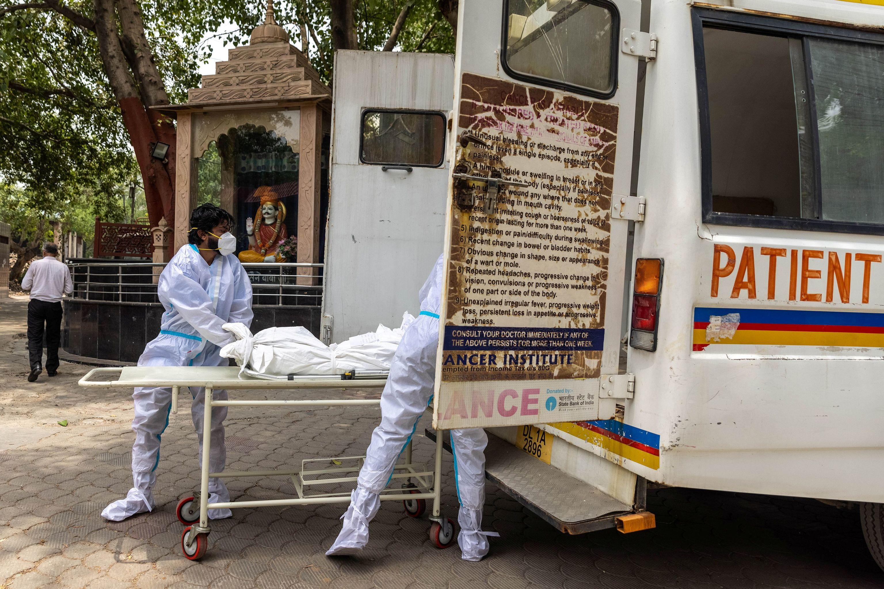 Dos sanitarios trasladan el cadáver de una víctima de coronavirus en Nueva Delhi.