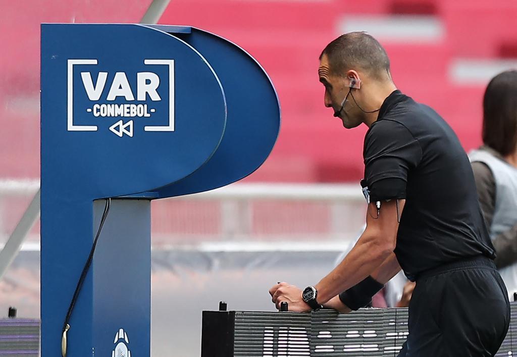 El árbitro, ante el VAR durante el reciente Ecuador-Perú