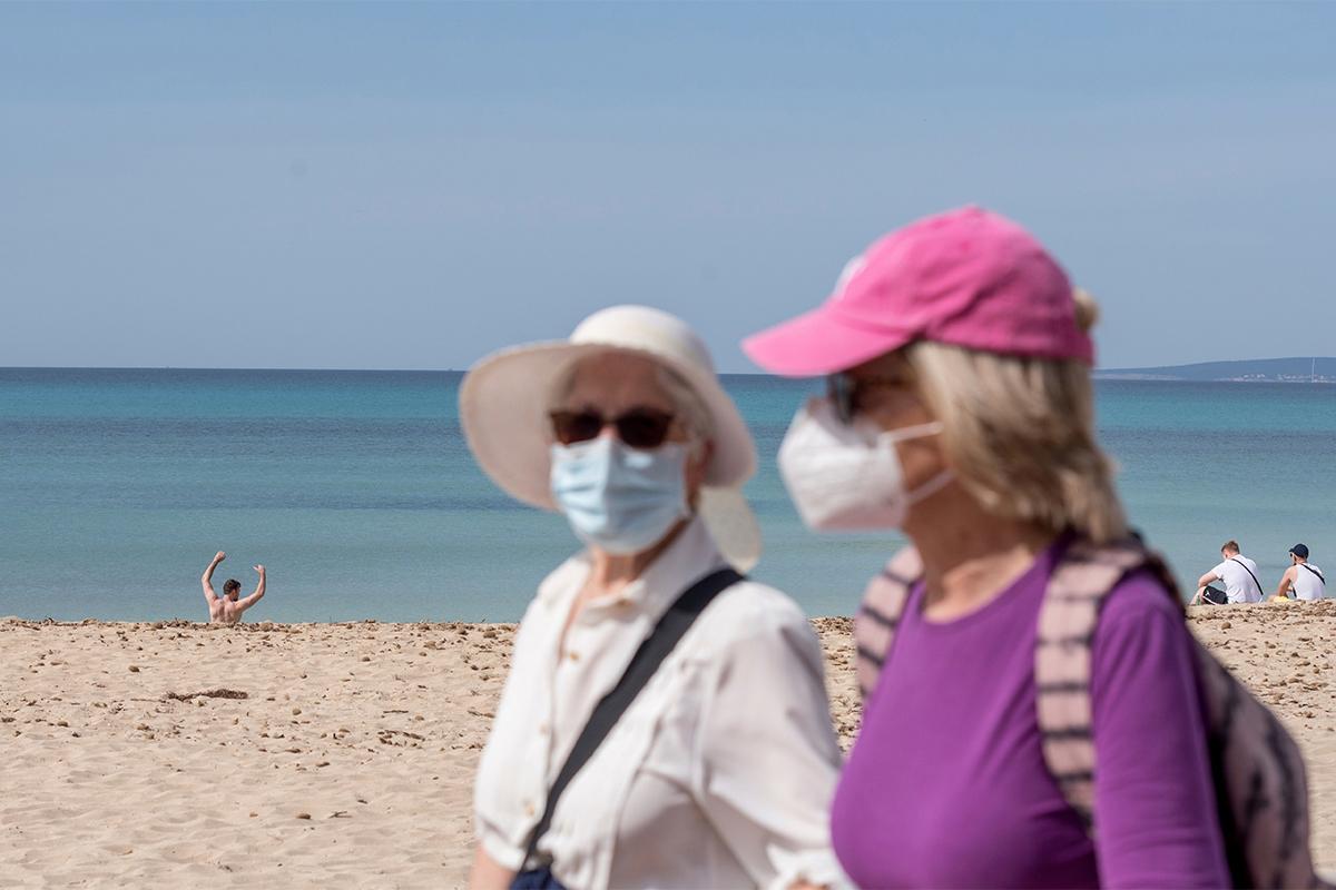 Turistas caminan por el paseo marítimo de la playa de Palma de Mallorca.