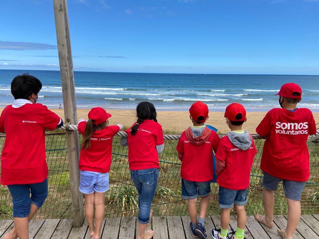 Una grupo de niños observa la playa limpia de residuos gracias al Programa Natura del Santander.