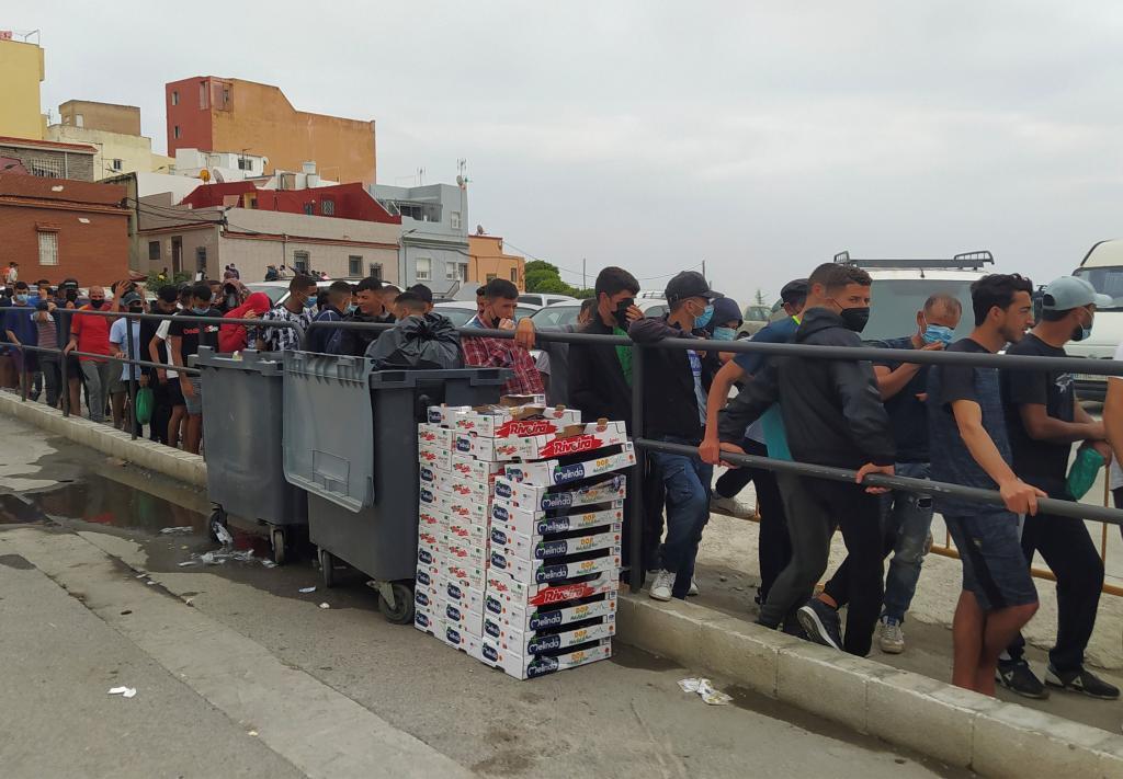 Un grupo de marroquíes hace cola para recibir comida de una ONG en Ceuta.