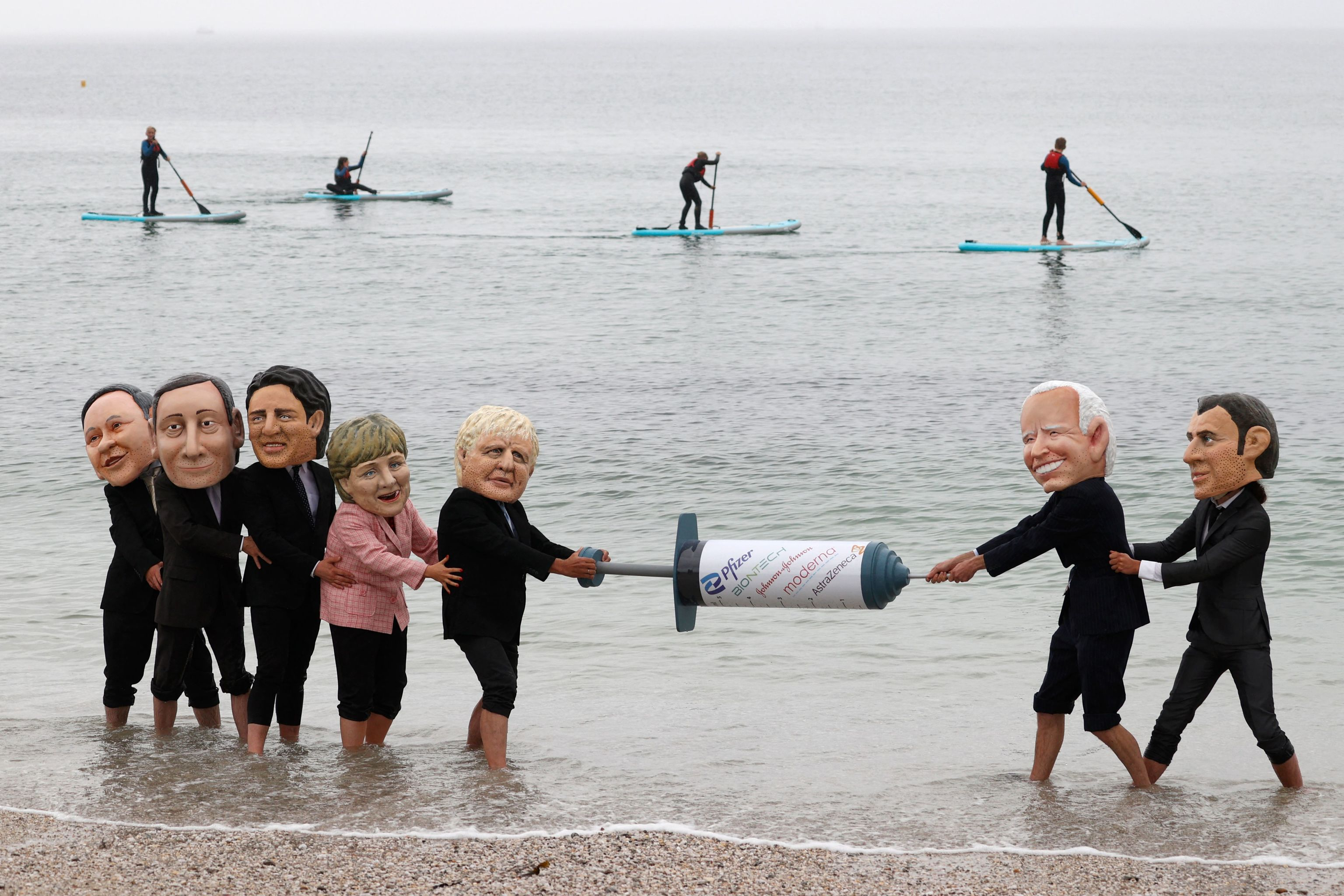 Activists representing the G7 leaders pull a 'vaccine' against Covid.