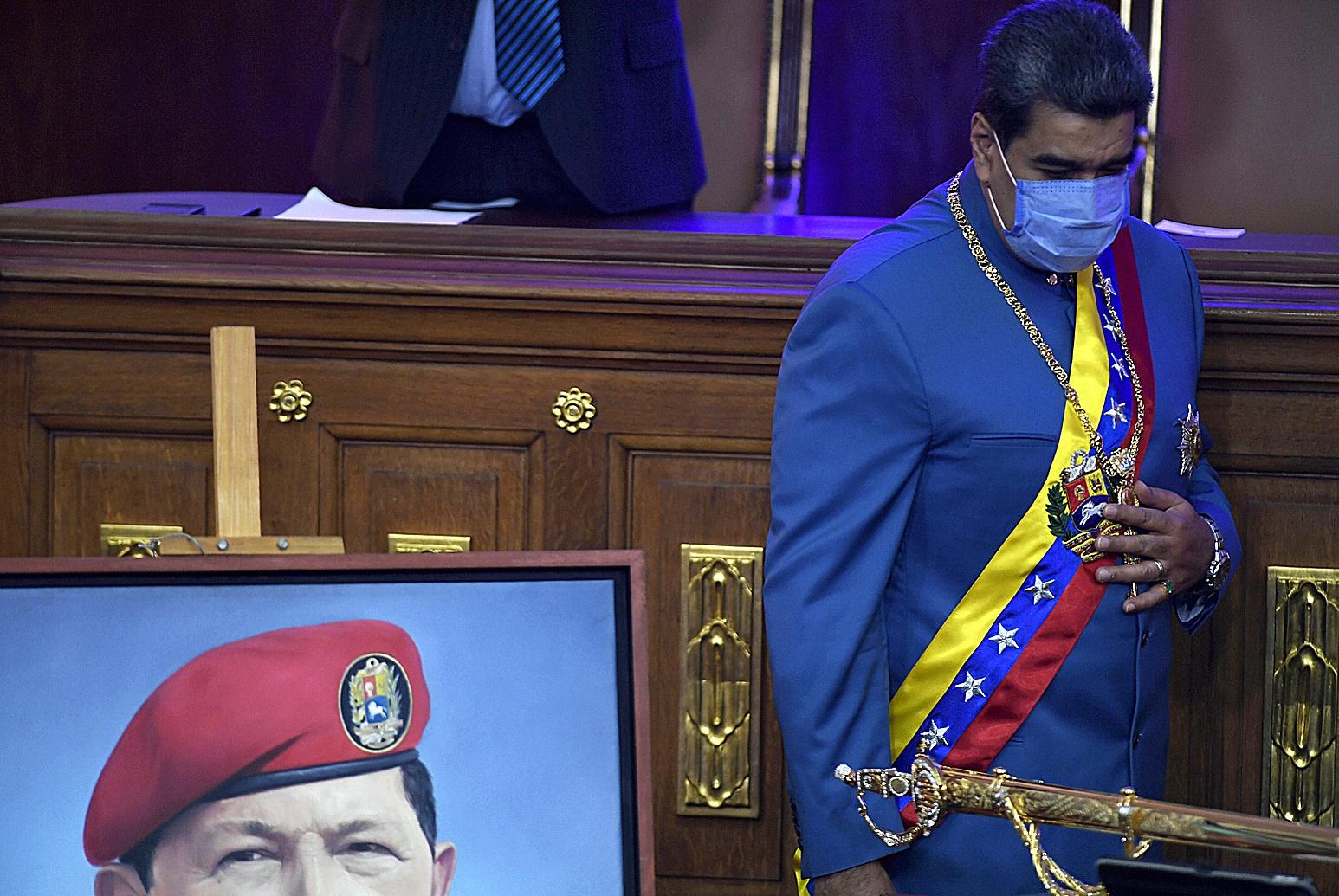 Nicolás Maduro junto a un retrato de Hugo Chávez.