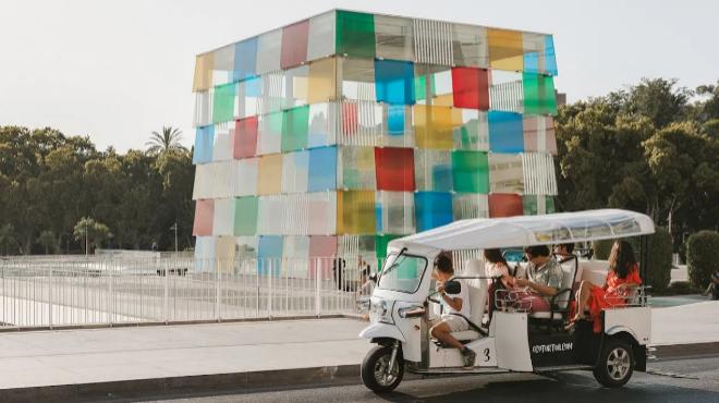 Un tuk-tuk pasa por delante del Museo Pompidou de Málaga.